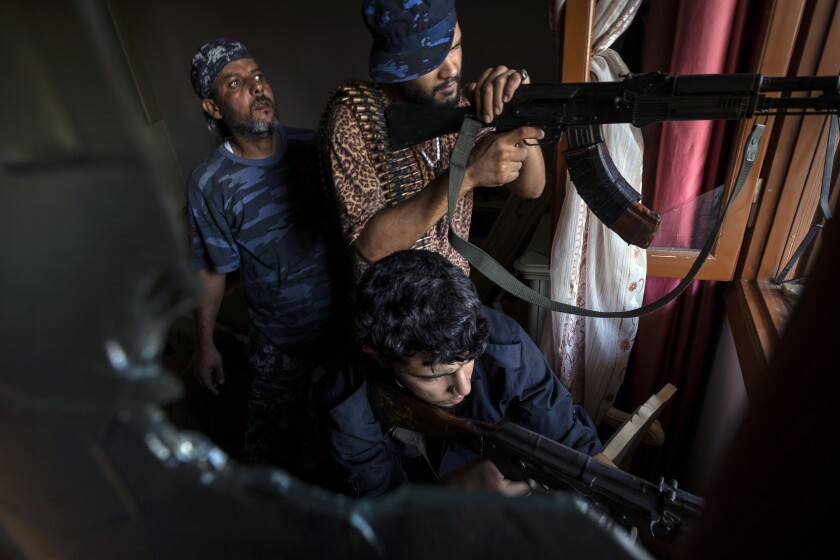 "FILE - In this Aug 31, 2019 file photo, fighters of the 'Shelba' unit, a militia allied with the U.N.-supported Libyan government, aim at enemy positions at the Salah-addin neighborhood front line in Tripoli, Libya. Two Libyan militia commanders and a Syrian war monitor group say Turkey is deploying Syrian extremists to fight in Libya's civil war. These extremists are affiliated with groups like al-Qaida and the Islamic State. They're fighting as mercenaries on behalf of the United Nations-supported government in Libya. The Libyan sources told The Associated Press that Turkey has airlifted more than 2,500 foreign fighters into Tripoli, and that ""dozens"" are extremist-affiliated. (AP Photo/Ricard Garcia Vilanova, File)"