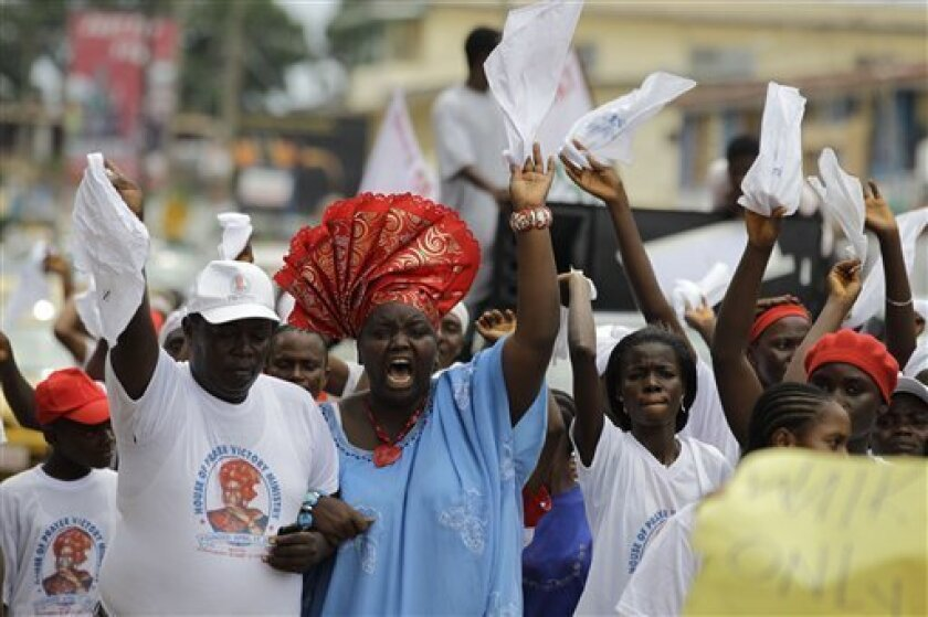 Members of a church group sing and dance as they march through the capital's streets calling for peaceful elections, in Monrovia, Liberia Monday, Oct. 10, 2011. Africa's first democratically elected female president, Ellen Johnson Sirleaf, who was honored this week with a Nobel Peace Prize, will face stiff competition at Liberia's presidential polls Tuesday against a fiery opposition candidate and his soccer-star running mate. (AP Photo/Rebecca Blackwell)