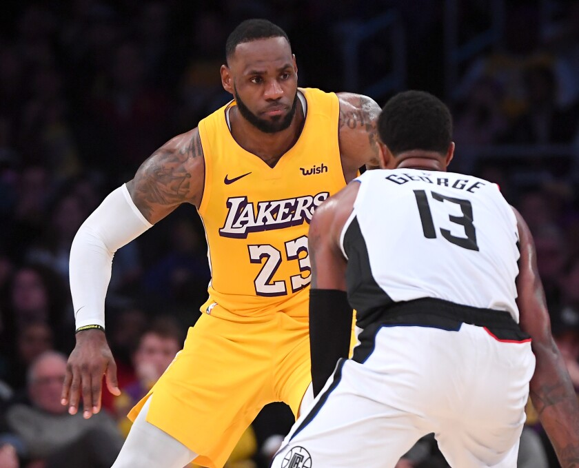 Lakers' LeBron James (23) guards Clippers' Paul George on Christmas Day at Staples Center. James will miss Saturday's game in Oklahoma City because of an illness.
