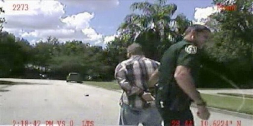 In this still image made from dash-cam video provided by the Lake Mary (Fla.) Police, George Zimmerman is detained by officers on Monday, Sept. 9, 2013. Police in central Florida have been focusing on a broken iPad in their investigation of a domestic dispute between George Zimmerman and his estranged wife Shellie this week. Shellie Zimmerman called 911, saying her estranged husband was in his truck and threatening her and her father with a gun. She also said her husband punched her father in th