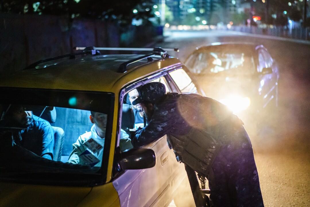 یک رزمنده مسلح با لباس فرم از پنجره اتومبیل بیرون می آید و سه نفر داخل آن هستند