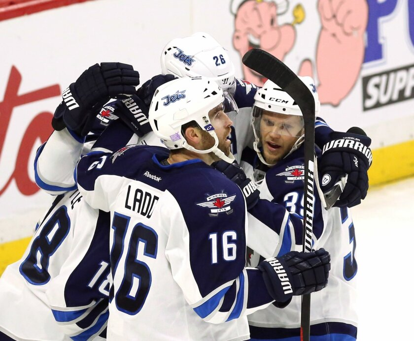 Winnipeg Jets' Andrew Ladd (16) celebrates his goal with teammates Toby Enstrom, right, Blake Wheeler, rear, and Bryan Little during the second period of an NHL hockey game against the Ottawa Senators on Thursday, Nov. 5, 2015, in Ottawa, Ontario. (Fred Chartrand/The Canadian Press via AP)