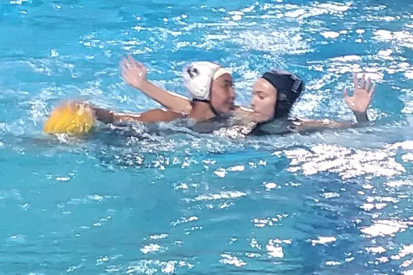 Sinalei Schwalger of Helix (left) draws defensive attention from Poway's Grace Kellerman in the San Diego Section Division I girls water semifinals on Wednesday. Poway prevailed 11-8. (Glae Thien photo).