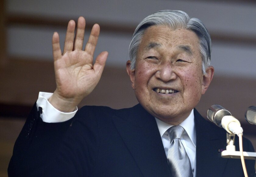 Japan's Emperor Akihito waves to well-wishers through bulletproof glass from a balcony during a 2016 New Year's public appearance in Tokyo.