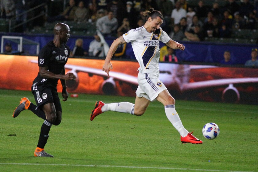 CARSON, CA - APRIL 08: Zlatan Ibrahimovic #9 of Los Angeles Galaxy dribbles past Ike Opara #3 of Sporting Kansas City toward the goal during a game against Sporting Kansas City at StubHub Center on April 8, 2018 in Carson, California.