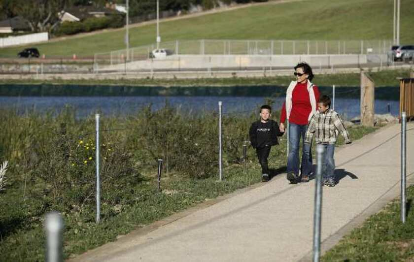 Lena Hayashi with grandsons Drew, right, and Scott Hayashi walk along the paths during the ribbon-cutting ceremony Wednesday afternoon for the Fairview Park Wetlands & Riparian Habitat.