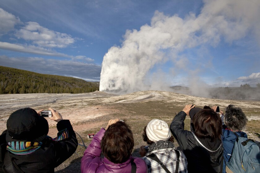 Tourists photograph Old Faithful at Yellowstone