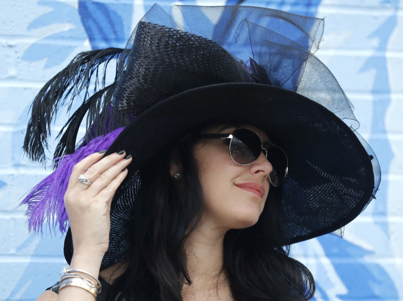 A woman shows off her hat before the 144th running of the Kentucky Derby.
