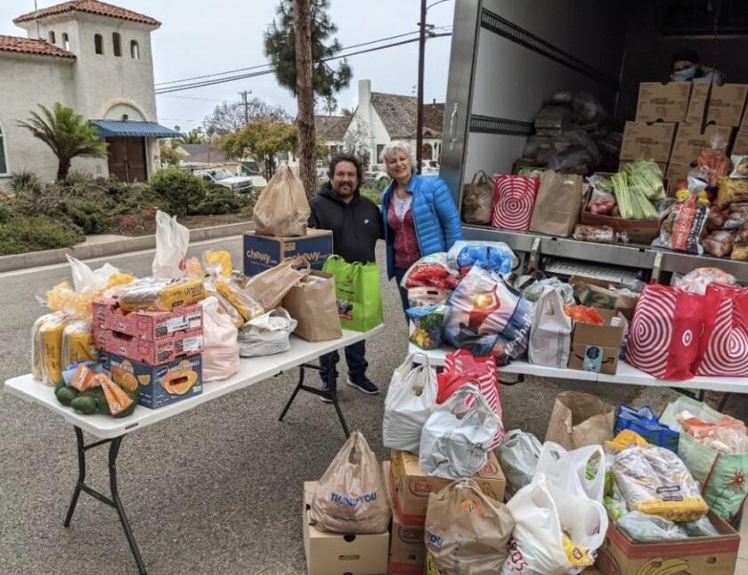 Oscar Ortega and Diana Shimkus with donated food.