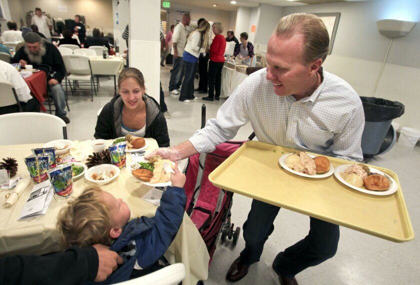 San Diego mayoral candidate Kevin Faulconer serves a turkey meal to 2-year-old Dustin Fry during the San Diego Rescue Mission's annual Thanksgiving dinner.