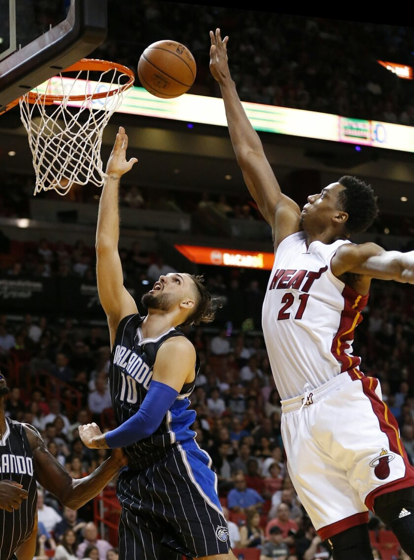 Miami Heat's Hassan Whiteside (21) defends against a shot by Orlando Magic's Evan Fournier (10) during the first half of an NBA basketball game, Friday, March 25, 2016, in Miami. (AP Photo/Joel Auerbach)