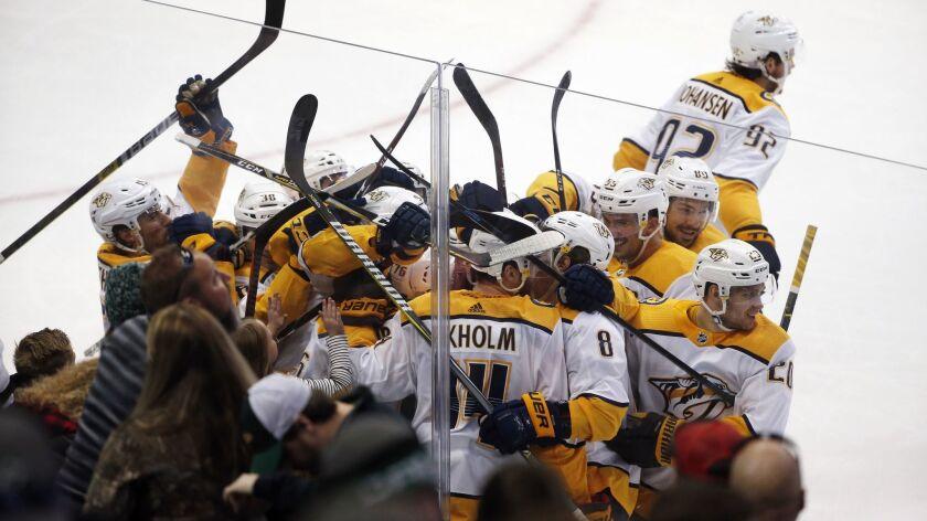 Nashville Predators defenseman Mattias Ekholm (14) is swarmed by teammates after his game-winning go