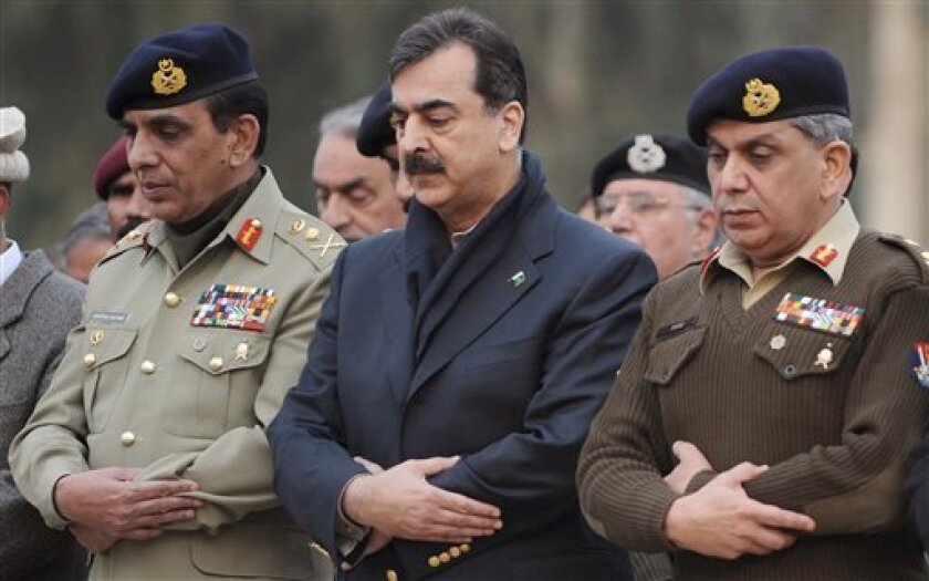 Pakistan's Prime Minister Yousuf Raza Gilani, center, and Army Chief Gen. Ashfaq Parvez Kayani, left, attend funeral prayer for an army officer, who was killed in the Friday's suicide bombing in a mosque, Saturday, Dec. 5, 2009, in Rawalpindi, Pakistan. A Taliban suicide squad targeted Pakistani military officers and their families praying at a mosque close to army headquarters in a gruesome display of the militants' ability to strike at the center of power. (AP Photo)