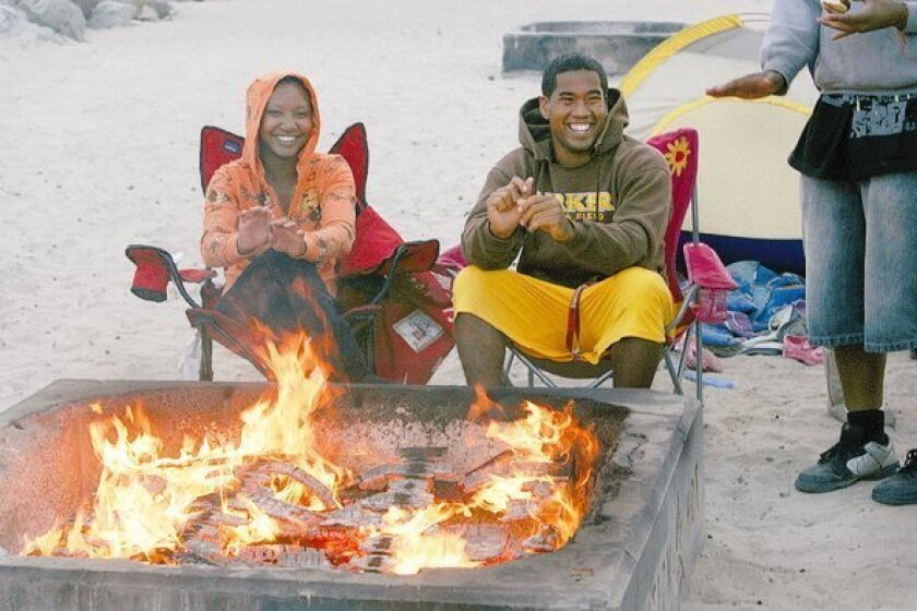 Tatiana Tobe, 17, and De'Anthony Tobe, 18, keep warm at a beach fire earlier this week. Private groups stepped in to raise money to keep the fire pits from being scuttled due to budget constraints in the City of San Diego.