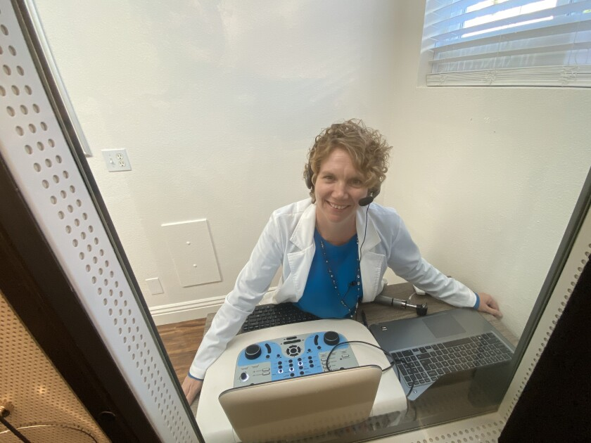 Audiologist Dr. Jerilyn Dutton appears as she does to her patients: behind the glass of the sound booth she uses to administer hearing tests to her patients.