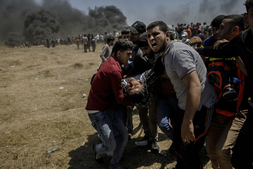 Palestinians carry an injured man during clashes with Israeli forces near the border between the Gaza Strip and Israel on Monday.