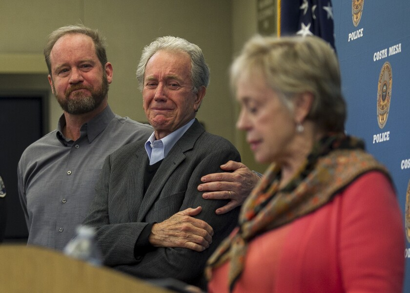 Scott Sudweeks, left, braces his father, Alan, as his mother, Sandy, speaks during a news conference about the 1997 cold-case rape and slaying of his sister Sunny Sudweeks at the Costa Mesa Police Department on Thursday.