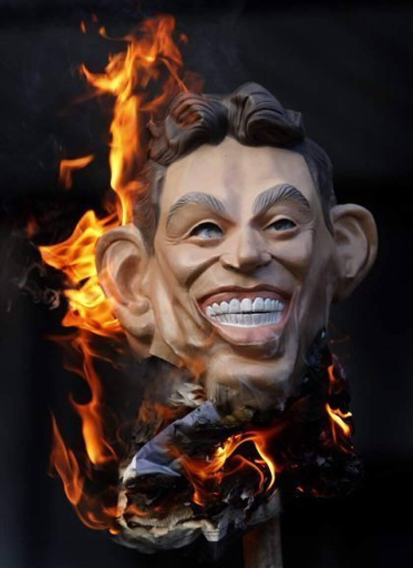 A mask of former British Prime Minister Tony Blair is burnt by a demonstrator outside the Iraq Inquiry in London, Monday, Nov. 30, 2009, where David Manning, a key adviser to former British Prime Minister Tony Blair  was testifying about decisions made before the Iraq war. The inquiry is the most e