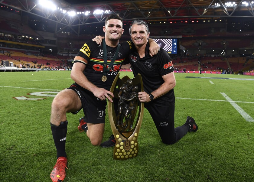 Nathan Cleary, left, and Ivan Cleary of the Penrith Panthers pose for a photograph following the National Rugby League grand final between the Panthers and South Sydney Rabbitohs in Brisbane, Sunday, Oct. 3, 2021. Ivan won a NRL grand final for the first time after two previous defeats as a coach and his son Nathan was named the player-of-the match as the Panthers beat the Rabbitohs 14-12 in the championship match at Brisbane. (Dave Hunt/AAP Image via AP)