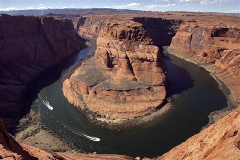 In this Wednesday, March 5, 2008 file photo, water levels at the Colorado River's Horseshoe Bend begin to rise along the beaches just hours after the Glen Canyon Dam jet tubes began releasing water, in Page, Ariz. Drought, climate change and an increasing population in the West are pushing the Col