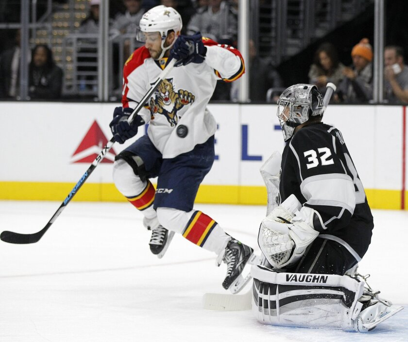 Florida Panthers center Vincent Trocheck, left, leaps to deflect a shot with Los Angeles Kings goalie Jonathan Quick (32) in net during the first period of an NHL hockey game in Los Angeles, Saturday, Nov. 7, 2015. (AP Photo/Alex Gallardo)
