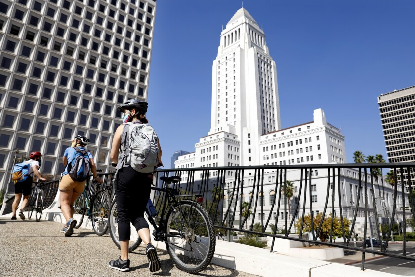 From left, Aimee Gilchrist, Marissa López, and Yvonne Condes, walk their bikes through downtown Los Angeles