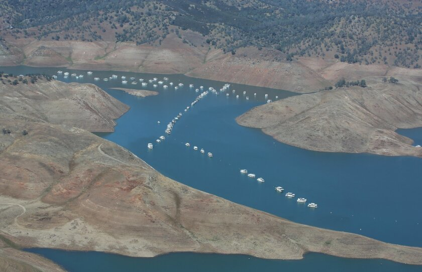 In this aerial photo taken Tuesday, April 28, 2015, house boats sit in the receding waters of Lake McClure in Mariposa County Northeast of Merced, Calif. The State Water Resources Control Board is considering sweeping mandatory emergency regulations to protect water supplies as water levels as some