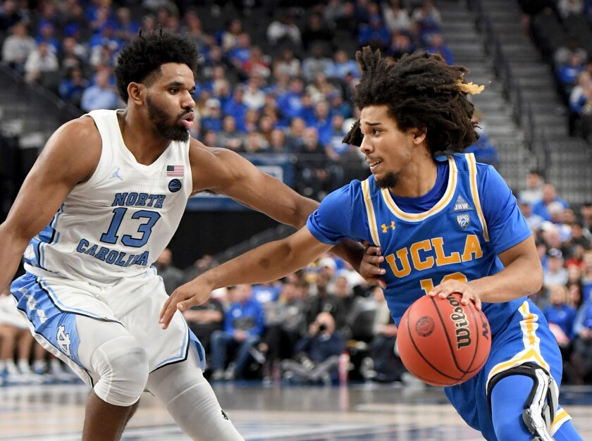 UCLA's Tyger Campbell drives against North Carolina's Jeremiah Francis on Dec. 21 at T-Mobile Arena in Las Vegas.