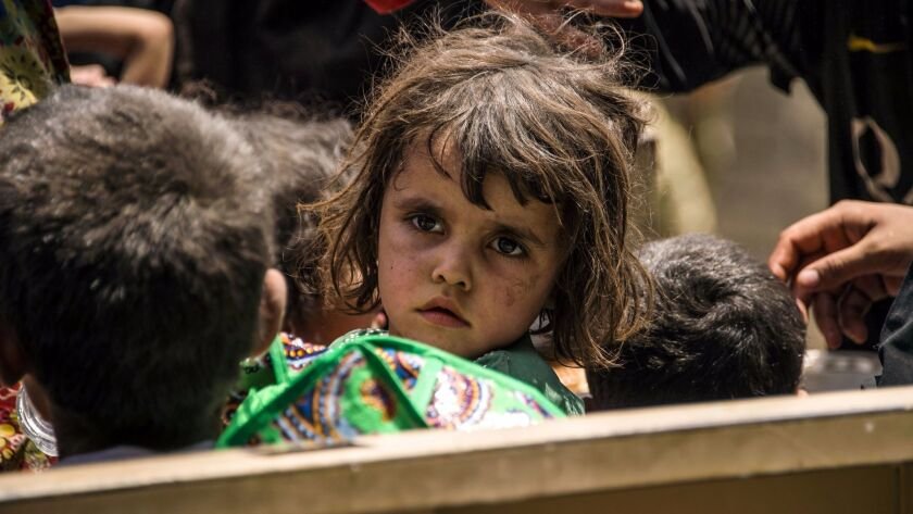 Iraqi children wait to be relocated after fleeing the fighting between government forces and Islamic