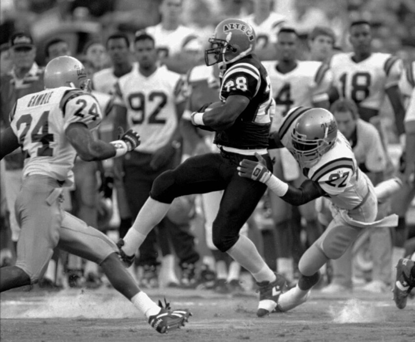 San Diego State running back Marshall Faulk can find no room to run as UCLA defenders Robert Gamble (24) and Marvin Goodman (22) close in during UCLA's 52-13 victory on Sept. 30, 1993, in San Diego. Faulk was held to 53 net yards rushing in the game.