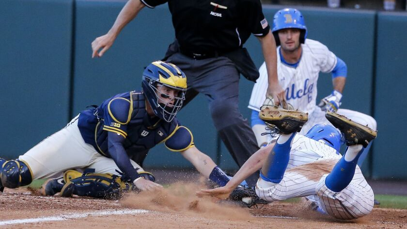 Michigan catcher Joe Donovan, front left, tags out UCLA's Jeremy Ydens, front right, during the four
