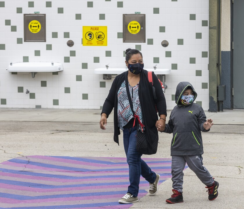 A student and his mother walk on campus