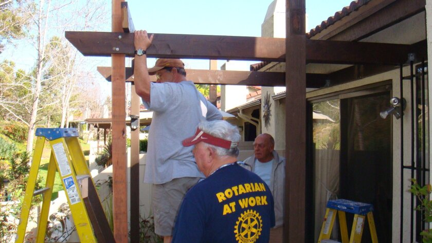 Rotary Home Team members Pete Fitzpatrick, foreground, Dan Daniels (on ladder) and Bill Wachtler, at rear, work on the patio.