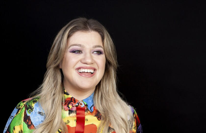 FILE - This April 14, 2019 file photo shows singer and actress Kelly Clarkson posing for a portrait at the Four Seasons Hotel in Los Angeles. Clarkson has been named the godmother of Norwegian Cruise Line's newest ship Norwegian Encore, and the pop star said she signed on to the project because it aligned with the things that's most important to her life: families spending time together, humanitarian work, and live music. (Photo by Rebecca Cabage/Invision/AP, File)