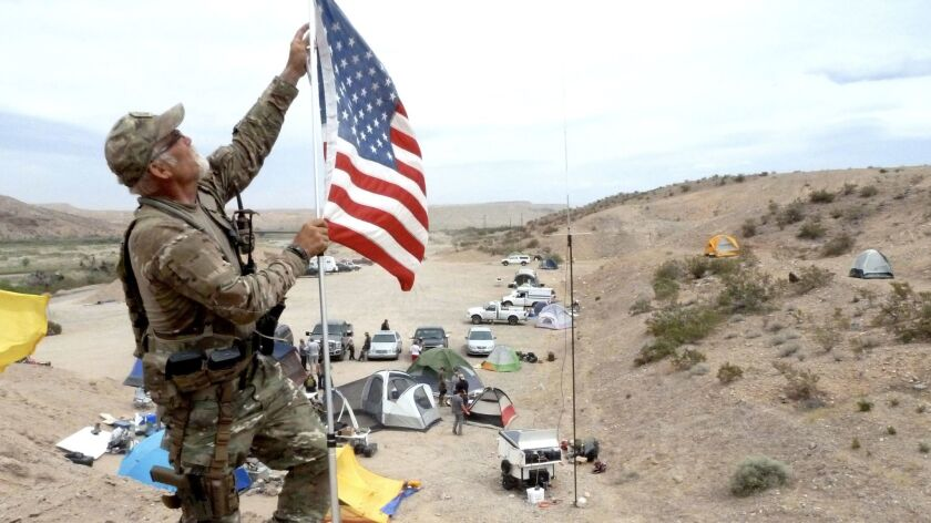 Jerry DeLemus fixes a U.S. flag near an armed militia camp in 2014 that rallied to the Bundy ranch to protect him from the U.S. government.