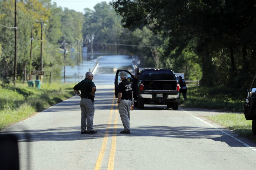 FILE - In this Sept. 19, 2018, file photo, responders congregate near where two people drowned the evening before when they were locked in a Horry County Sheriff's department transport van while crossing an overtopped bridge over the Little Pee Dee River on Highway 76, during rising floodwaters in the aftermath of Hurricane Florence in Marion County, S.C. The estates of the South Carolina women who drowned filed lawsuits last week in Horry County alleging negligence by a company that created policies and procedures for the law enforcement agency. (AP Photo/Gerald Herbert, File)