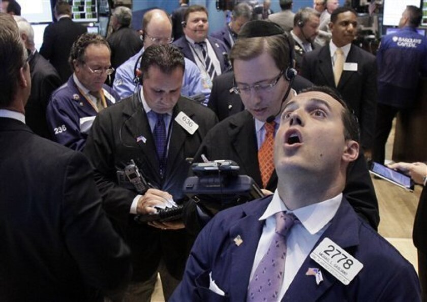 Specialist Michael Gagliano, foreground right, calls out prices at his post on the floor of the New York Stock Exchange Tuesday, Oct. 4, 2011. (AP Photo/Richard Drew)