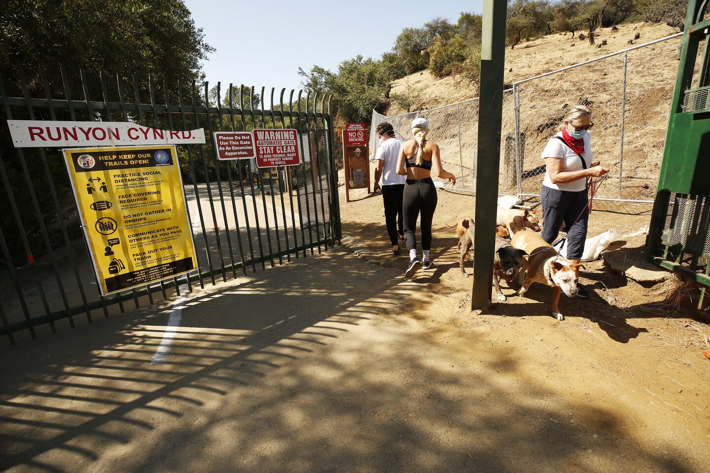 LOS ANGELES, CA - MAY 27: Hikers enter Runyon Canyon Park at the North entrance on Mulholland Drive in the Hollywood hills on Wednesday morning as the popular park has been reopened and is closely monitored by L.A. City person new under COVID-19 safety guidelines. Visitors are still required to wear masks at the park and people are instructed to walk in lanes with directional arrows trying to maximize social distancing. Hollywood on Wednesday, May 27, 2020 in Los Angeles, CA. (Al Seib / Los Angeles Times)