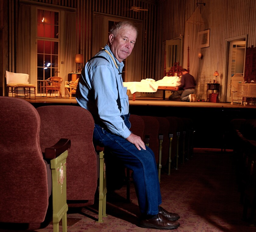 Ned Beatty perches on the arm of a theater seat in front of a stage dressed for a play.