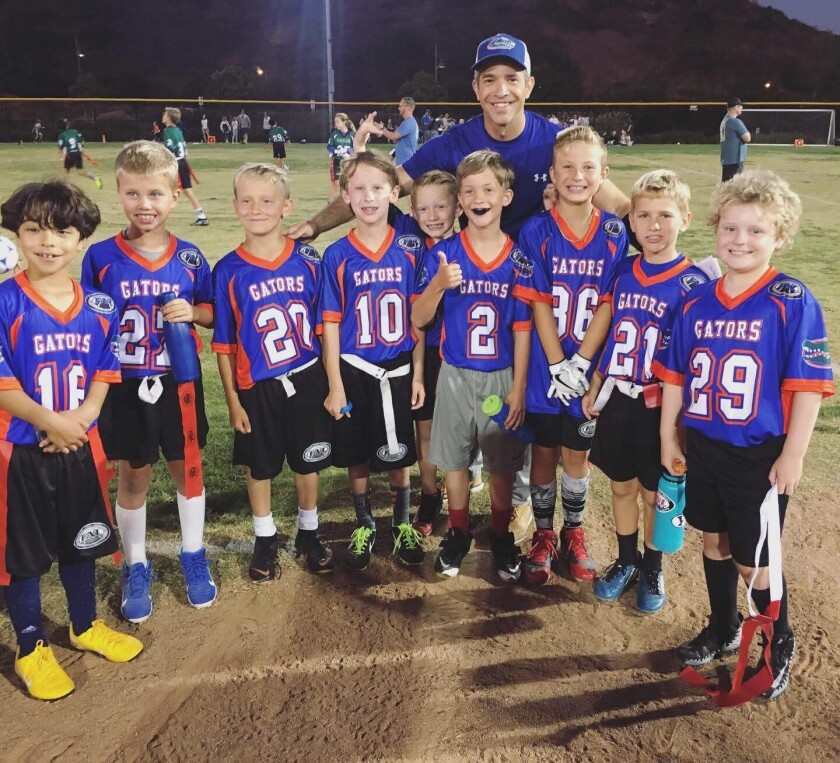 Fox 5 San Diego anchor and debut author Andrew Luria is shown coaching the flag football team of his son, Nathan (No. 2).