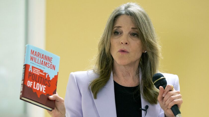 "Marianne Williamson holds up a copy of her book ""A Politics of Love."""