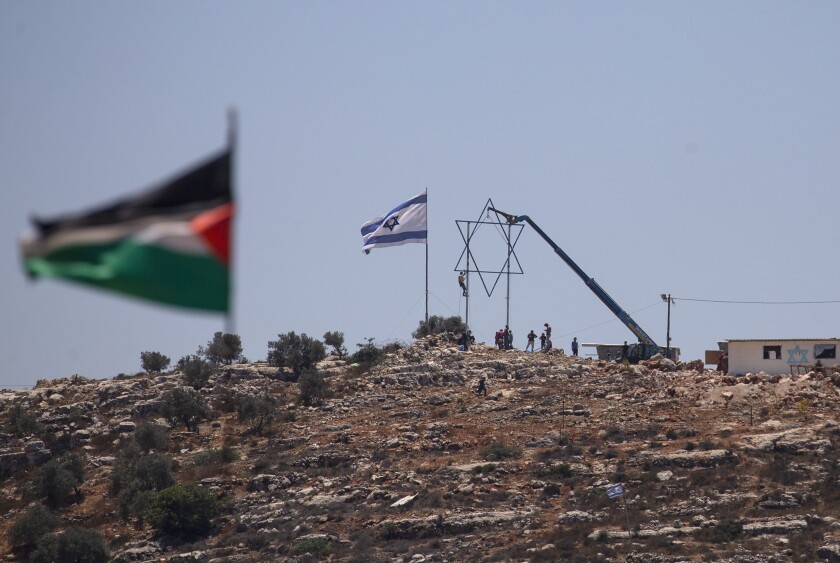 Israeli settlers adjust a large Star of David in the recently established wildcat outpost of Eviatar as it seen from the nearby Palestinian village of Beita, near the West Bank city of Nablus, Friday, July 2, 2021. Israel has reached a compromise with Jewish settlers which they will leave by the end of the week and the area will become a closed military zone, but the houses and roads will remain in place. (AP Photo/Majdi Mohammed)