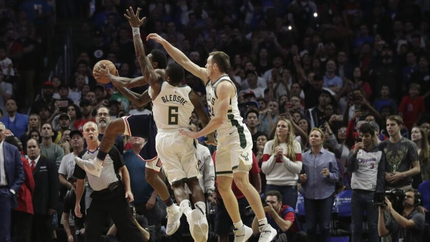 Clippers' Lou Williams puts up a shot while defended by Milwaukee Bucks' Eric Bledsoe and Pat Connaughton with less than two seconds left in overtime.