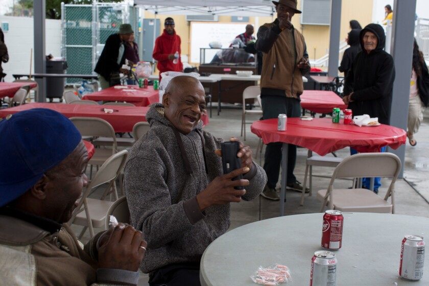 Residents joke around during a holiday lunch held at a shelter in Watts.