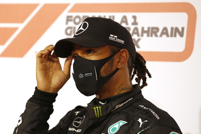 Formula One champion Lewis Hamilton in a hat and mask