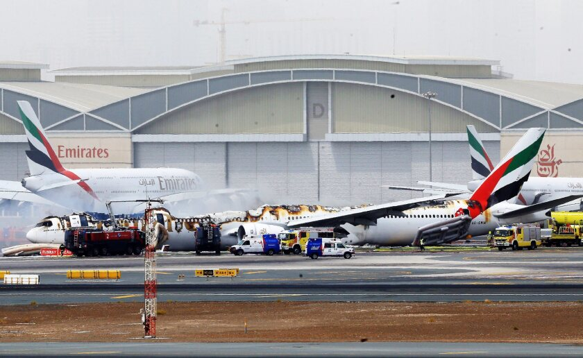 An Emirates Boeing passenger jet lies on the ground at Dubai International Airport after being gutted by a fire following a crash-landing Aug. 3, 2016.