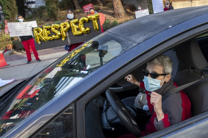 """LINCOLN HEIGHTS, CA - DECEMBER 02: Nurse Helena Harvilicz, right, dances in her car to Aretha Franklin's """"Respect"""" at Keck Hospital of USC where nurses are protesting unsafe working conditions at the hospital Wednesday, Dec. 2, 2020 in Lincoln Heights, CA. (Brian van der Brug / Los Angeles Times)"""