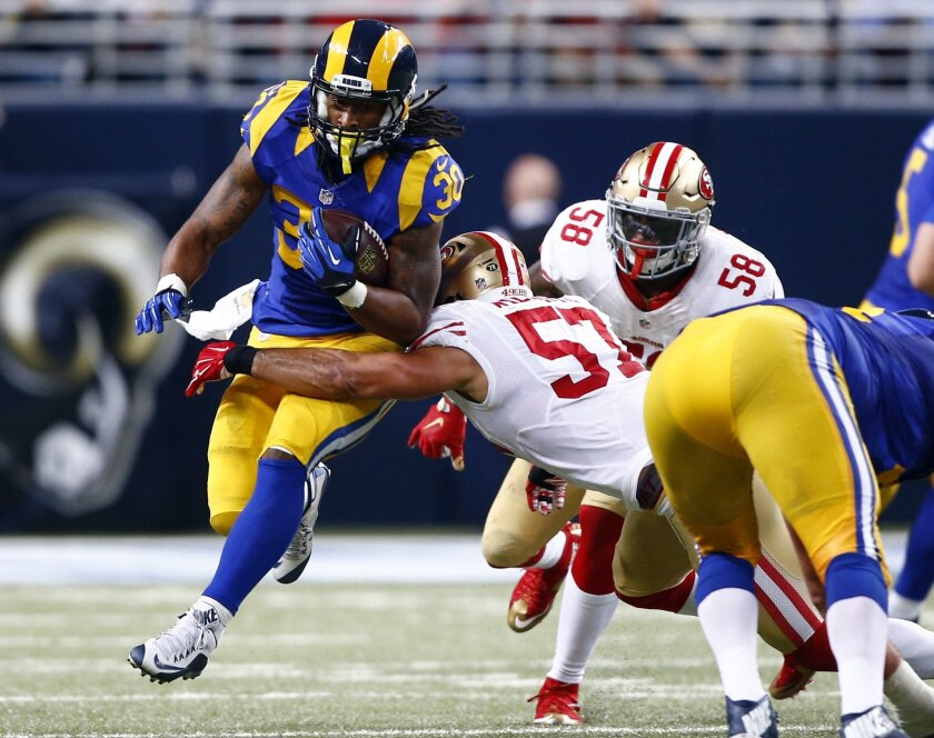 St. Louis Rams running back Todd Gurley, left, runs for a first down as San Francisco 49ers inside linebacker Michael Wilhoite and outside linebacker Eli Harold (58) defend during the third quarter of an NFL football game, Sunday, Nov. 1, 2015, in St. Louis. (AP Photo/Billy Hurst)