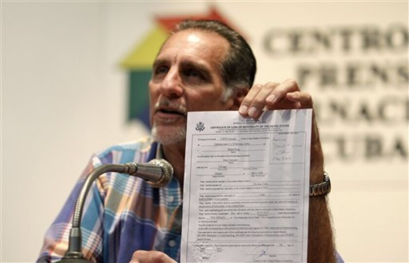 """Cuban agent Rene Gonzalez, 56, holds up his U.S. certificate of loss of nationality during a press conference in Havana, Cuba, Friday, May 10, 2013. Gonzalez who spent 13 years in a U.S. prison renounced his American citizenship Monday, May 6, 2013, as part of a deal that allows him to avoid returning to the United States to serve out the remainder of his probation. Gonzalez is one of the so-called """"Cuban Five"""" intelligence agents convicted in 2001 of spying on U.S. military installations in Sou"""
