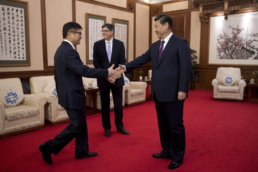 U.S. Ambassador to China Gary Locke, left, shakes hand with Chinese President Xi Jinping before they and U.S. Treasury Secretary Jacob Lew, center, meet at the Diaoyutai State Guesthouse in Beijing.